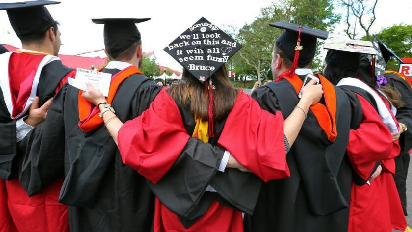 Los estudiantes se abrazan en la ceremonia de graduación de Rutgers en Piscataway, Nueva Jersey (Mel Evans / Associated Press).