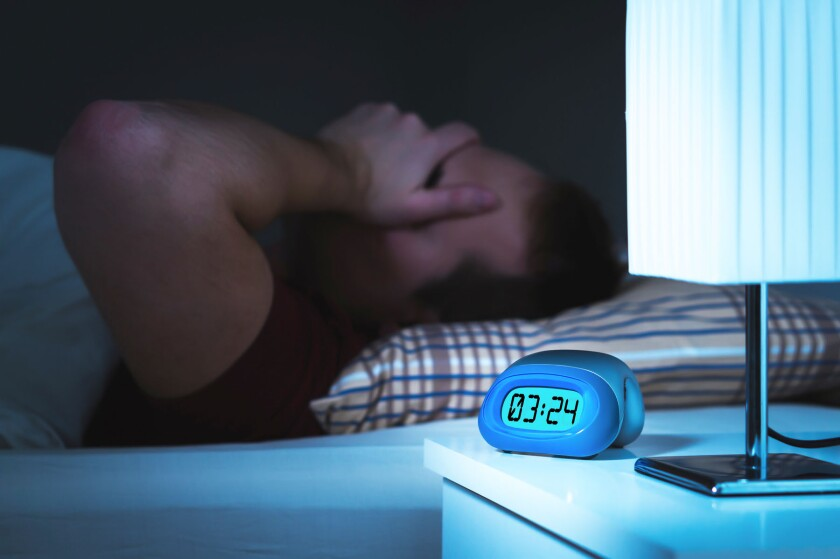 a person in bed who can't sleep. clock shows 3:24