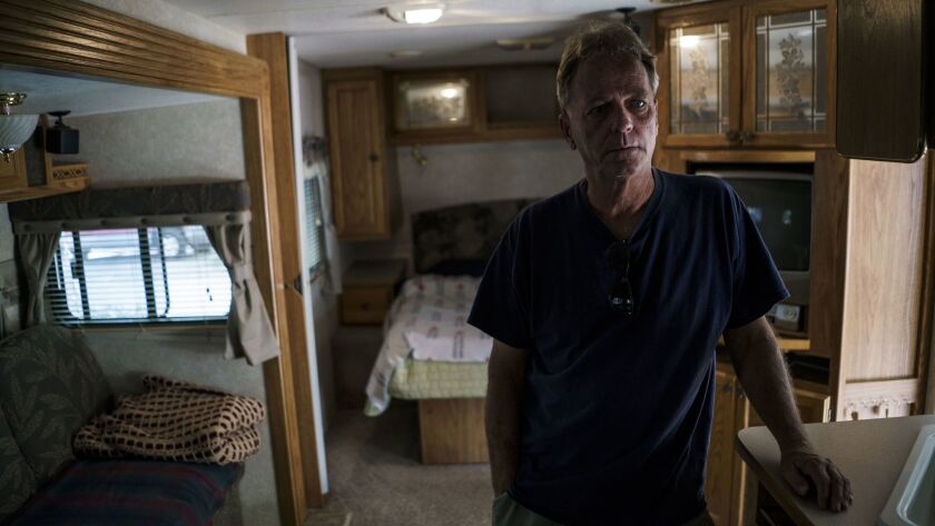 Raymond Taylor looks around the temporary trailer where he and his wife Linda have lived for more th