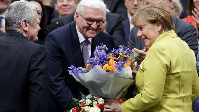 German President-elect Frank-Walter Steinmeier, center, is congratulated by German President Joachim Gauck and Chancellor Angela Merkel on Sunday. Steinmeier takes office March 18.