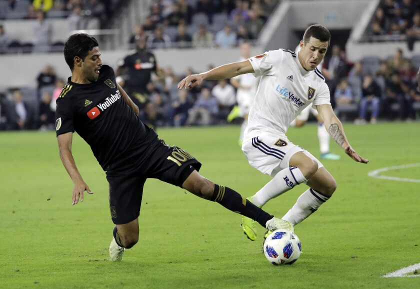 Los Angeles FC's Carlos Vela, left, is defended by Real Salt Lake's Aaron Herrera during the first half of an MLS soccer playoff match Thursday, Nov. 1, 2018, in Los Angeles.