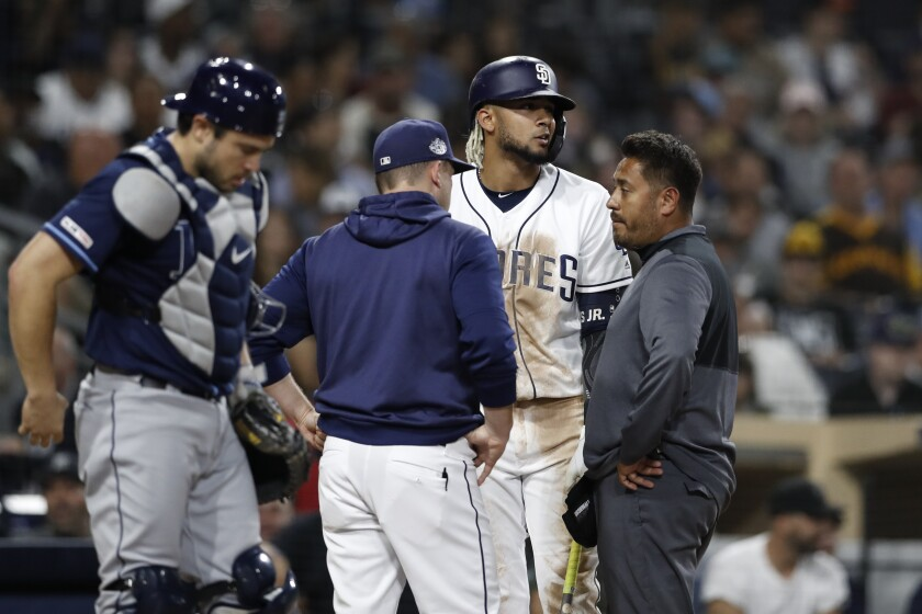 Padres' Fernando Tatis Jr., second from right, talks with manager Andy Green, second from left, and trainer Michael Salazar during an at-bat as Tampa Bay Rays catcher Mike Zunino stands at left during the sixth inning of Tuesday's game.