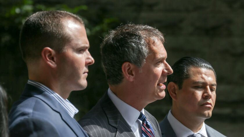 Attorney Ron Kaye, flanked by Los Angeles County sheriff's deputies Robert Lindsey, left, and Charles Rodriguez, holds a news conference outside the Clara Shortridge Foltz Criminal Justice Center in downtown Los Angeles.