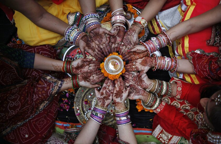 In this Oct. 30, 2015, file photo, Indian Hindu married women perform rituals on Karva Chauth festival in Ahmadabad, India. Married women decorate their hands with henna on Karva Chauth festival and observe a fast to pray for the longevity and well being of their husbands. (AP Photo/Ajit Solanki, F