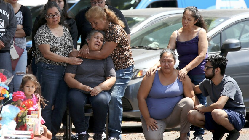 Relatives and friends grieve at a makeshift memorial at 9th Street and Locust Avenue in Long Beach,
