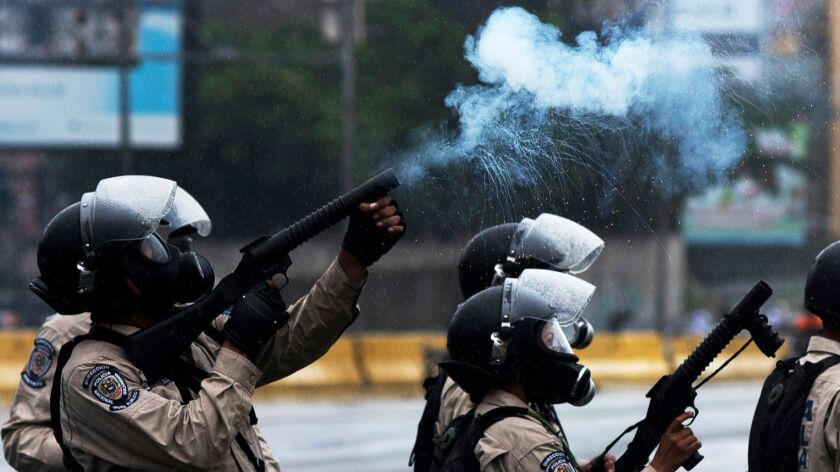 Venezuelan National Guard personnel in riot gear crack down on a march of opposition activists prote