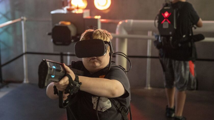 "Jack Dion, left, 10, and Kyle Mendoza, 14, of Santa Ana play at the location-based virtual reality start-up called ""Terminator Salvation: Fight for the Future"" in the former Red Robin building at the Irvine Spectrum Center."