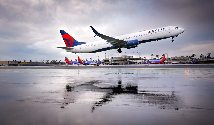 A Delta Airlines Boeing 737 is reflected in water while taking off from San Diego International Airport