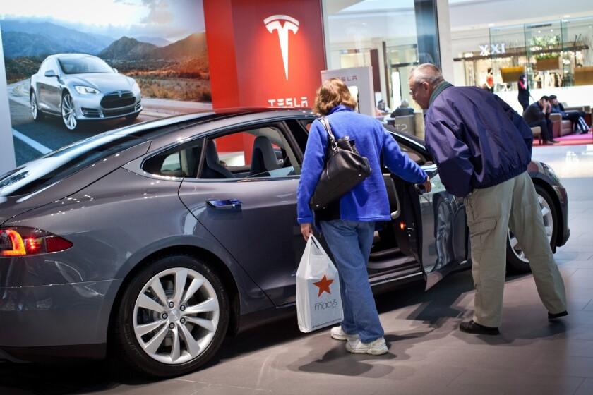 Barbara and Robert Hackett look inside a Tesla Motors Inc. Model S at the company's store at the Short Hills Mall in Short Hills, N.J.