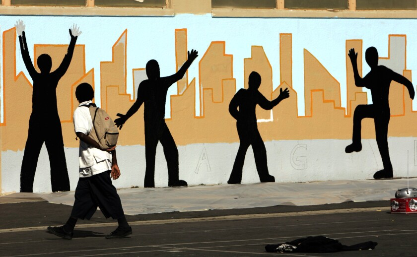 Some criminologists say expanding family-support programs in gang-plagued neighborhoods may be more effective than rehabilitating offenders. Above, a student walks past a landscape mural at Markham Middle School in Watts.