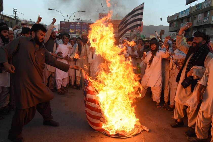 Pakistani Sunni Muslim supporters of a hard-line pro-Taliban party torch a U.S. flag during a protest of the drone strike that killed the Taliban's leader.