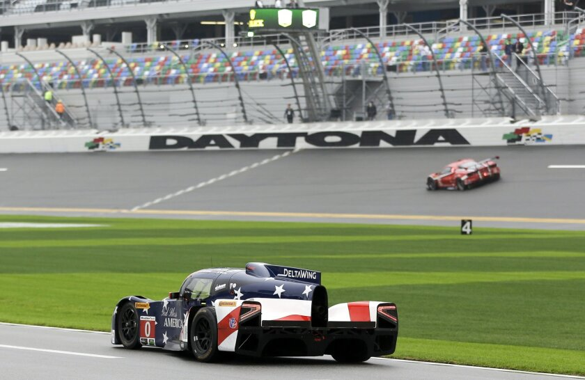 The DeltaWing Racing DWC13, front, heads down pit road during practice for the IMSA 24 hour auto race at Daytona International Speedway, Thursday, Jan. 28, 2016, in Daytona Beach, Fla. (AP Photo/John Raoux)