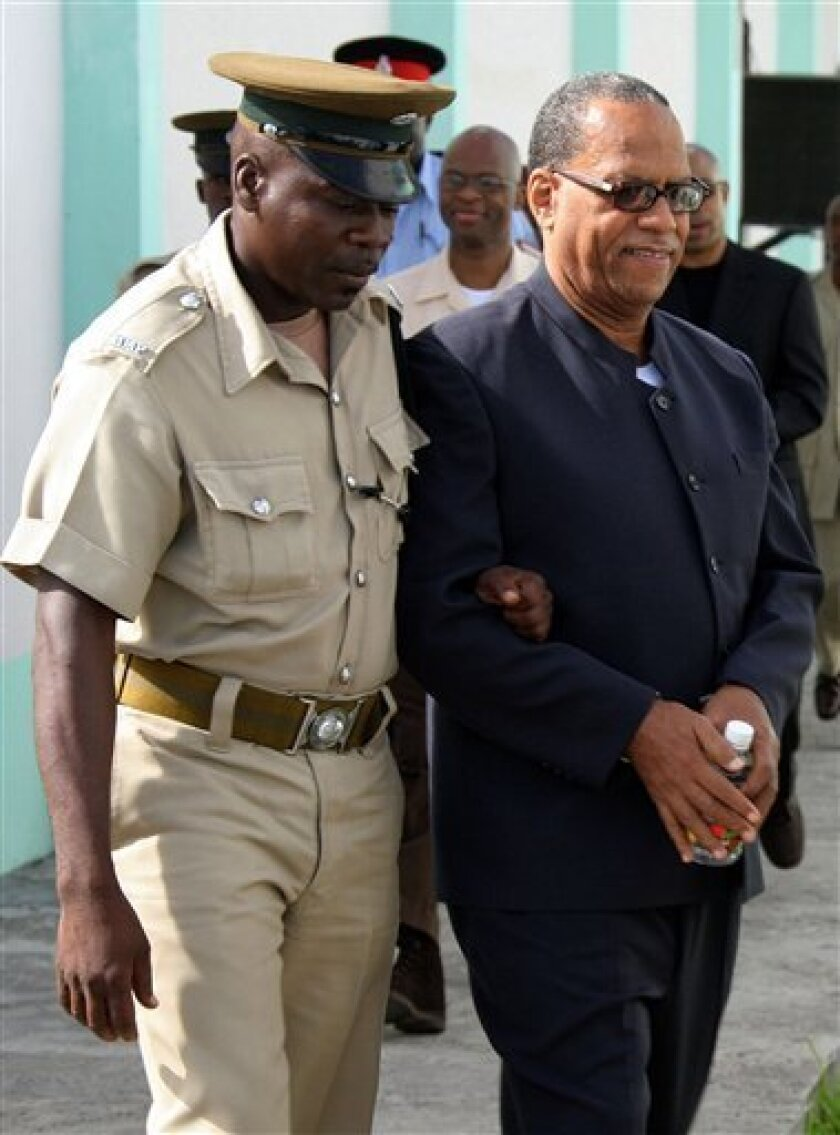 FILE - In this Monday, June 18, 2007 file photo, Grenada's former Deputy Prime Minister, Bernard Coard, right, is escorted by a prison guard upon his arrival to the Grenada Supreme Court for a re-sentencing hearing in St. George's, Grenada. Former Deputy Prime Minister Bernard Coard and six other men convicted of killing Grenada's leader in the 1983 coup that triggered a U.S. invasion strode out of prison on Saturday, Sept. 5, 2009, the last of 17 who had been sentenced for the crime. (AP Photo/Harold Quash, file)