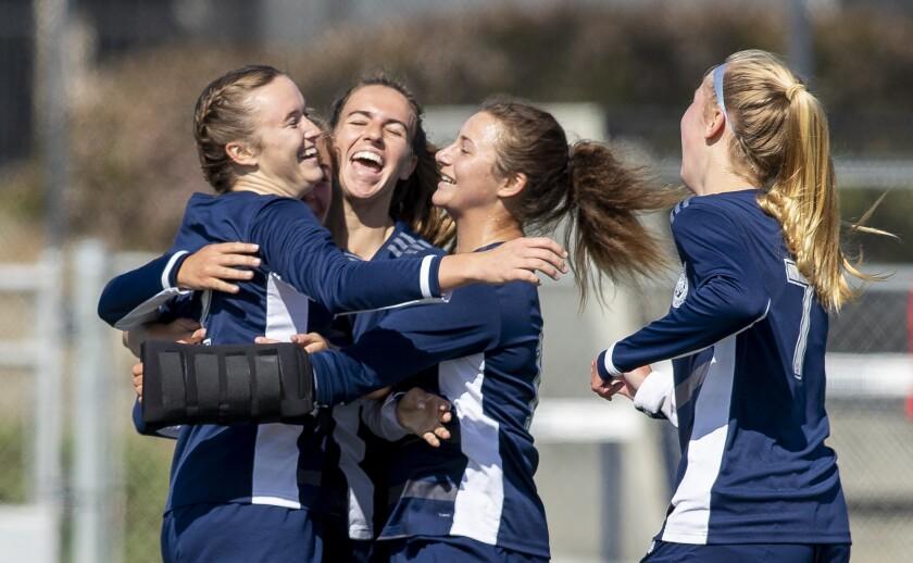 Newport Harbor teammates hug Laine Briggs, left, after she scored a goal against Corona del Mar.