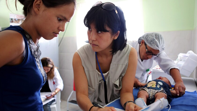 Dr. Megumi Itoh, center, an epidemic intelligence officer with the U.S. Centers for Disease Control and Prevention, helps investigate a Zika outbreak in Brazil.
