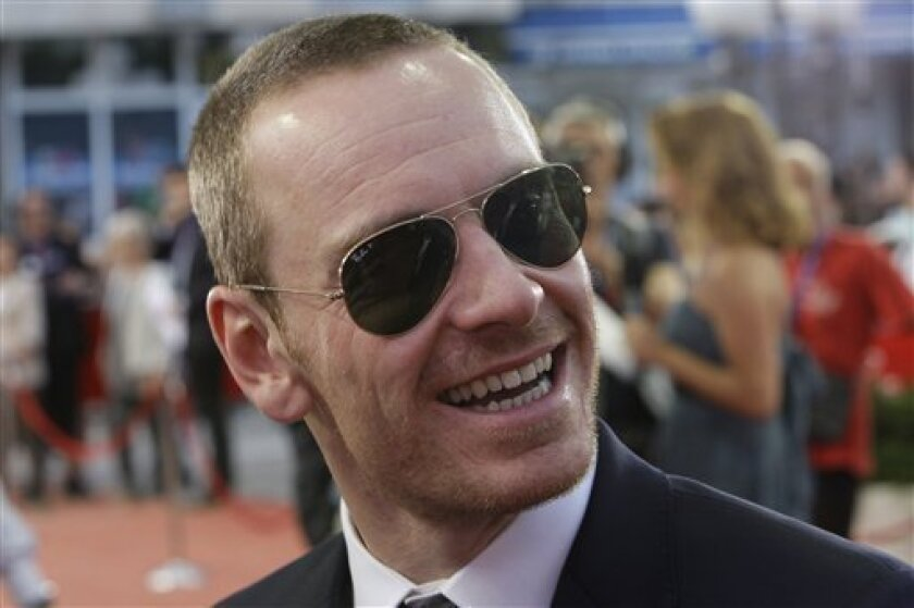 "In this July 27, 2011 file photo, German-born Irish actor Michael Fassbender arrives at the entrance to the Bosnian National Theatre for the 17th Sarajevo Film Festival, in Sarajevo. Now Fassbender is back in London for his latest film ""Jane Eyre,"" where his brooding and doleful Mr. Rochester runs smack into Mia Wasikowska's timid but fiercely feministic Jane. Set in Yorkshire, England, in the early 19th century, Charlotte Bronte's classic tale of the young governess who falls hopelessly in love with her employer has been told countless times. In addition to scores of TV, radio and stage adaptations, there have been least 17 movies, with the first full-length feature film dating back to 1914.(AP Photo/Amel Emric, file)"