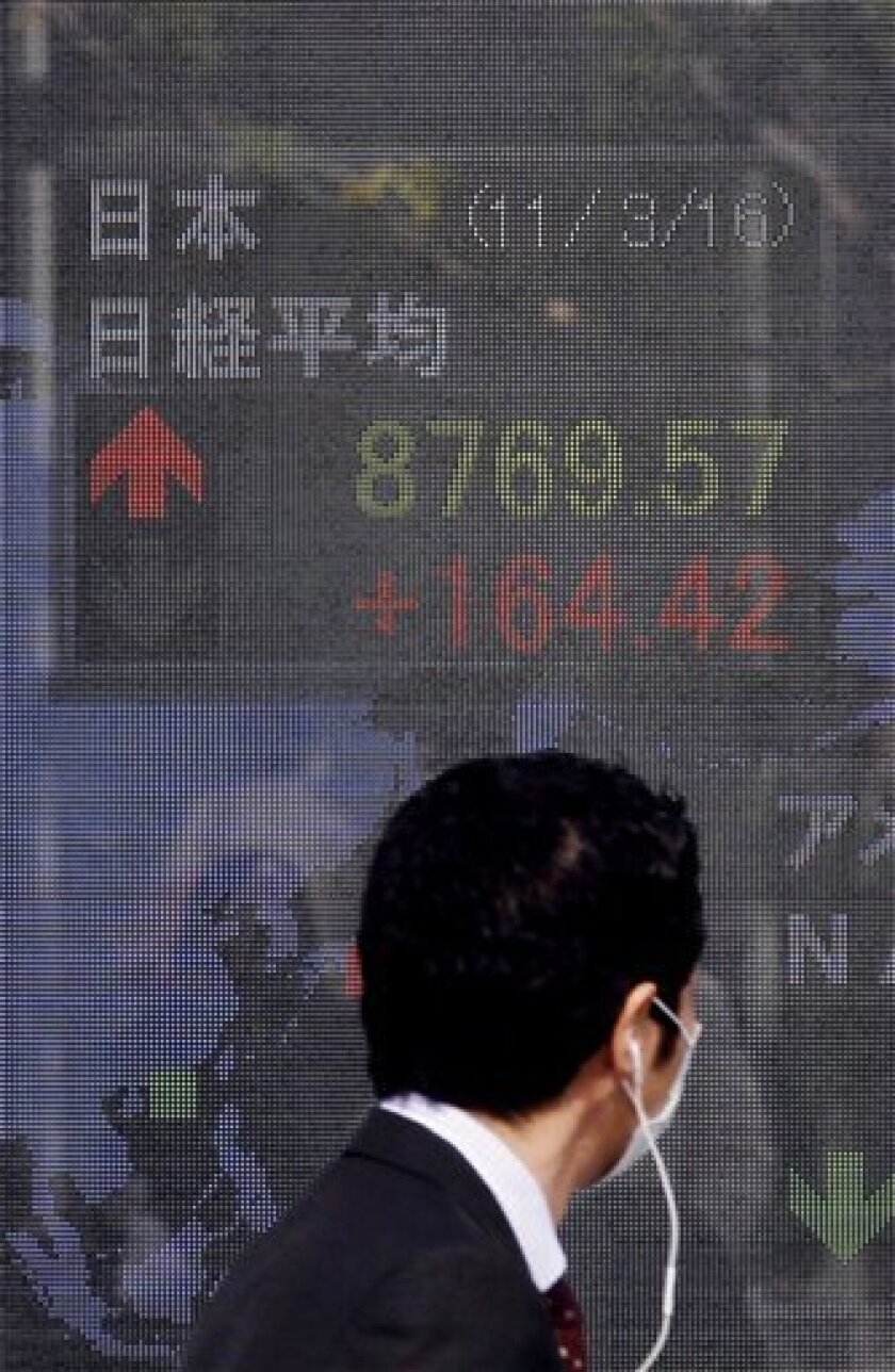 A man looks at the stock price board on a steet Wednesday, March 16, 2011 in Tokyo, Japan. (AP Photo/Eugene Hoshiko)