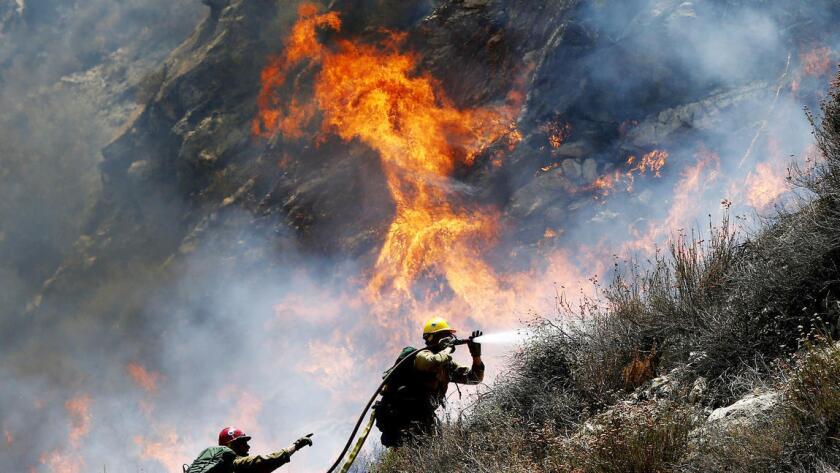 Los bomberos luchan contra el fuego junto a Soledad Canyon Road, cerca de Agua Dulce, este martes (Luis Sinco/Los Angeles Times).