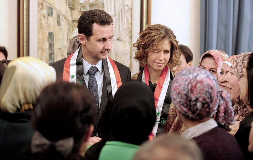 Syrian President Bashar Assad and his wife, Asma, meet with teachers last week in Damascus. Rebels reportedly killed Assad's cousin, Hilal, on Sunday.