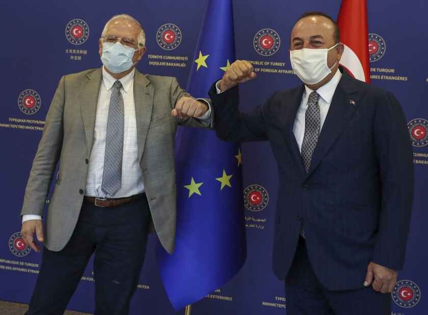 Turkey's Foreign Minister Mevlut Cavusoglu, right, and Josep Borrell Fontelles, High Representativeand Vice-Presidentof the European Commission, greet each other by using their elbows before their talks, in Ankara, Turkey, Monday, July 6, 2020. Cavusoglu and Borrell have discussed Turkey-EU relations, regional issues, Libya and Syria. (Cem Ozdel/Turkish Foreign Ministry via AP, Pool)