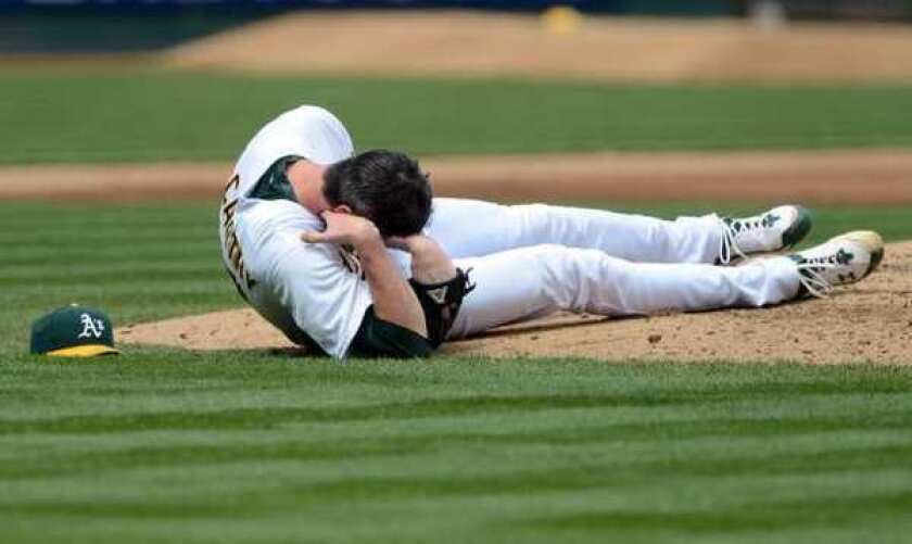 Oakland pitcher Brandon McCarthy holds his head after being hit by a line drive.