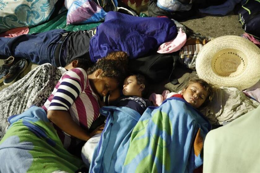 Migrantes hondureños fueron registrados este lunes al descansan en su campamento en el jardín Hidalgo de Tapachula, en el estado de Chiapas (México). EFE