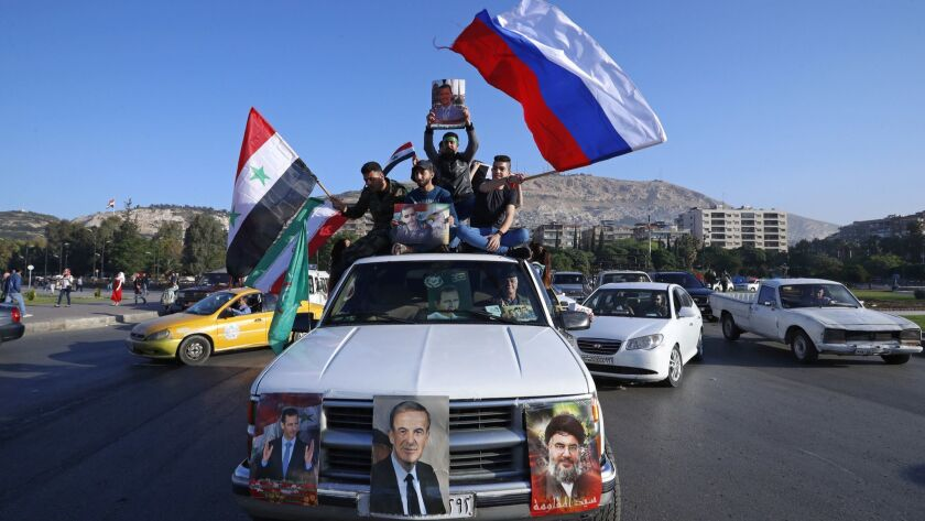 Syrian government supporters wave Syrian, Iranian and Russian flags as they chant slogans against the United States in Damascus on April 14.