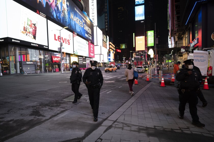 Police officers patrol New York's Times Square on foot, Wednesday night, April 29, 2020.