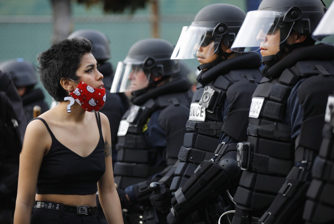Nikki Sanchez, 18, stands in front of San Diego police officers during a youth-led protest.