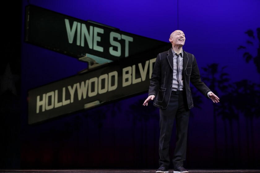 Francis Jue stands on a stage with a Hollywood and Vine street sign projected behind him.