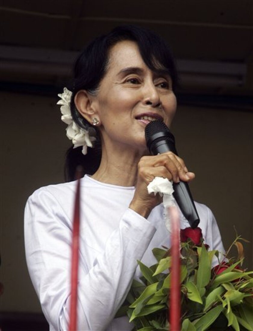 Myanmar pro-democracy leader Aung San Suu Kyi talks to supporters at the headquarters of her National League for Democracy party in Yangon, Myanmar Monday, April 2, 2012. Suu Kyi claimed victory Monday in Myanmar's historic by-election, saying she hoped it will mark the beginning of a new era for the long-repressed country. (AP Photo/Khin Maung Win)