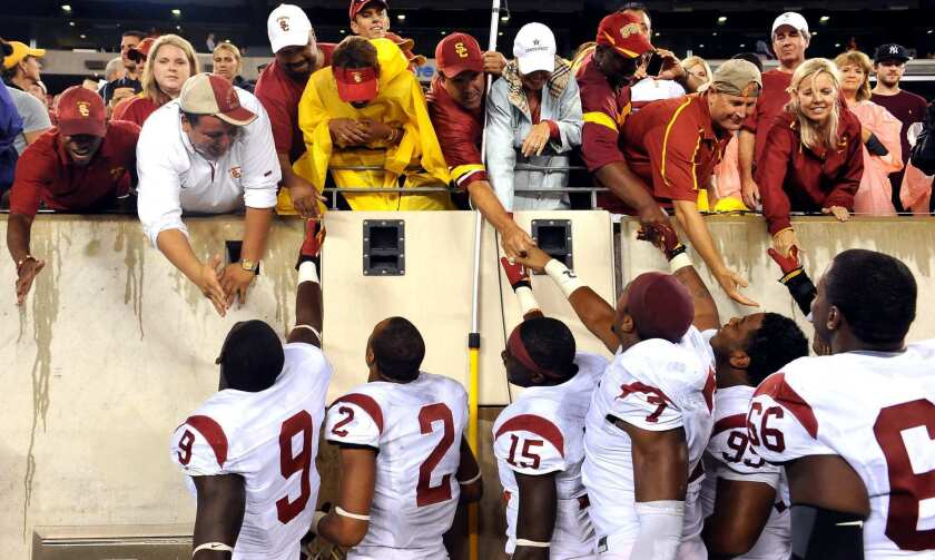 USC football players reach up to the stands to greet family at a game before the pandemic.