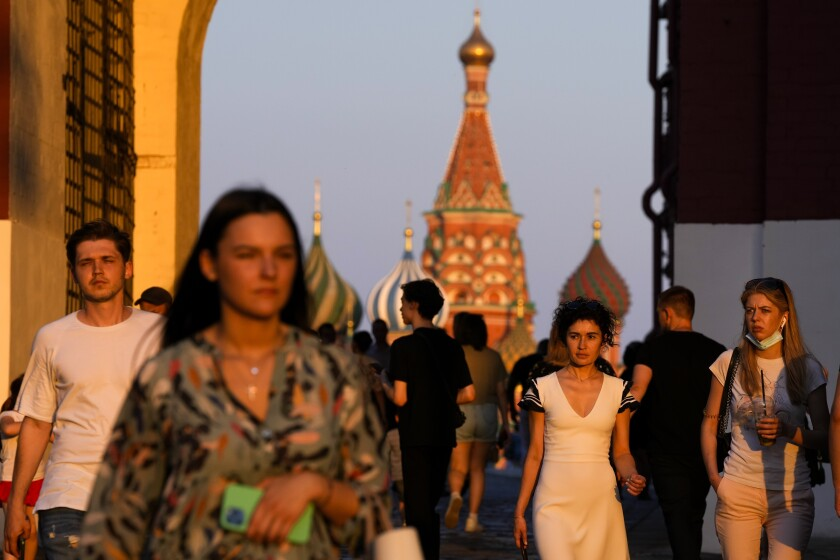 People, most of them without face masks, walk at Red Square during sunset in Moscow, Russia, Thursday, June 24, 2021. An ambitious plan of vaccinating 30 million Russians by mid-June against the coronavirus has fallen short by a third, and the country has started to see a surge in daily new infections. (AP Photo/Alexander Zemlianichenko)