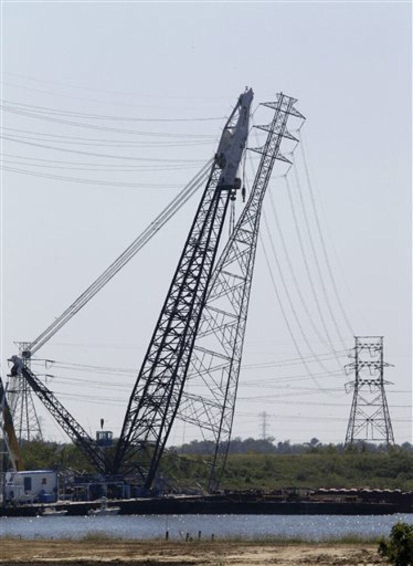 A crane helps pull a damaged electrical tower upright in the Houston Ship Channel Monday, Oct. 4, 2010 in Baytown, Texas. Barges struck the tower Sunday shutting down a key stretch of the channel and potentially causing a nearly $1 billion economic loss. (AP Photo/Pat Sullivan)
