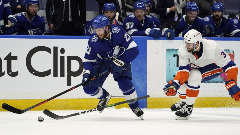 Tampa Bay Lightning center Brayden Point (21) gets around New York Islanders defenseman Adam Pelech (3) during the second period in Game 1 of an NHL hockey Stanley Cup semifinal playoff series Sunday, June 13, 2021, in Tampa, Fla. (AP Photo/Chris O'Meara)