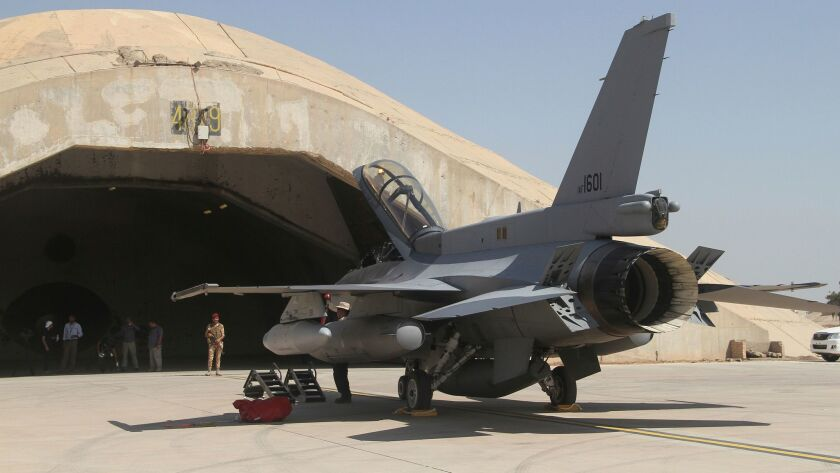 An F-16 fighter jet stands outside a hardened hangar at Balad Air Base, north of Baghdad, Iraq in July 2015.