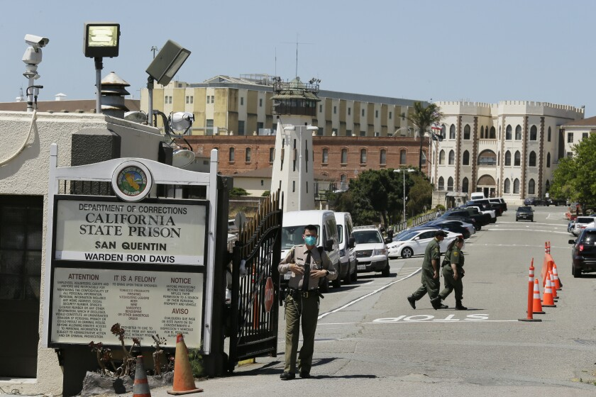 A correctional officer stands at the main gate of San Quentin State Prison in San Quentin, Calif.
