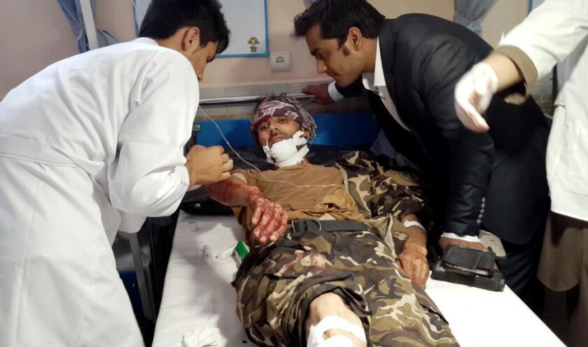 Afghan medical staff help an injured man at a hospital after a suicide attack in Faryab province on July 22.