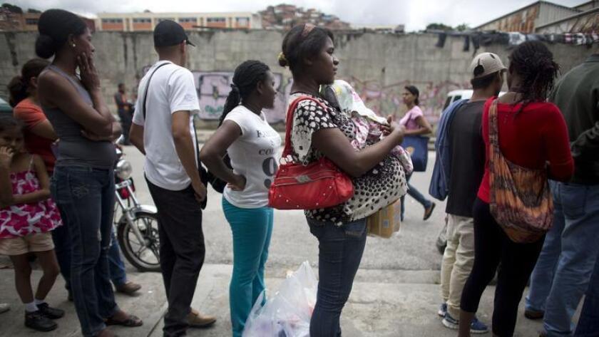 Foto de archivo de venezolanos en una fila en el exterior de un supermercado para comprar comida en Caracas.