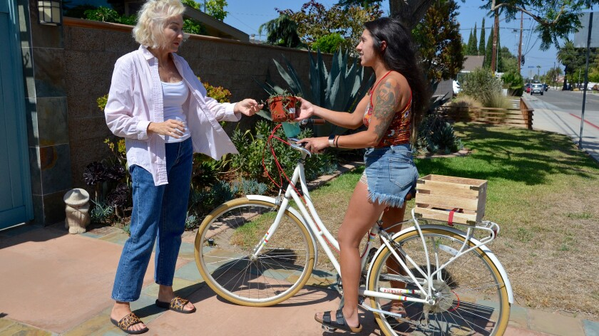 Christine Bliss hands a gifted plant to fellow member Lisa Chavera as part of the Buy Nothing Costa Mesa group.