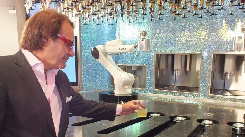 Owner Rino Armeni collects a cocktail freshly blended by one of the two robotic bartenders deployed