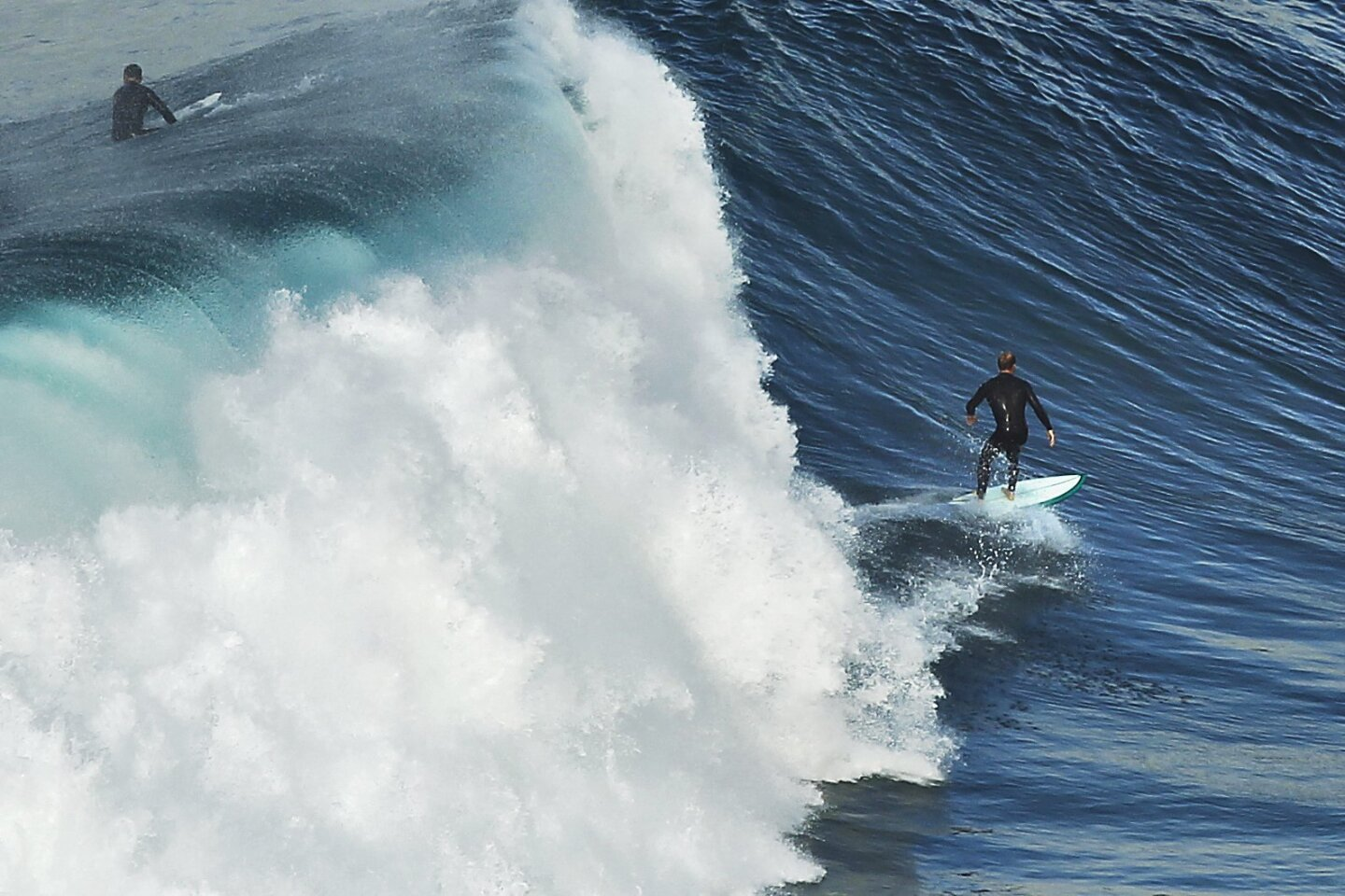 A surfer rides a wave at Black's Beach in La Jolla.