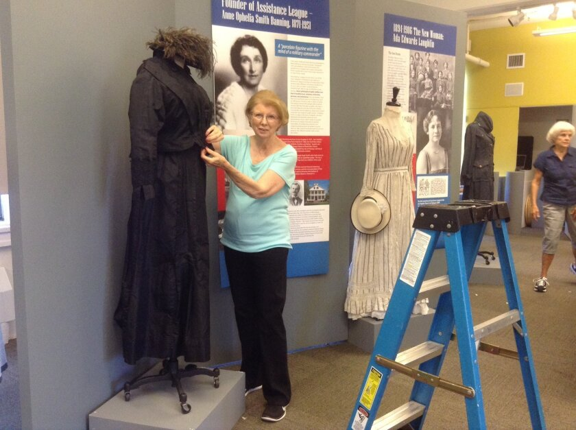 Maggie Brasch, past president of the San Diego Chapter of the Assistance League, helps prepare for the new exhibit at the Women's Museum of California.