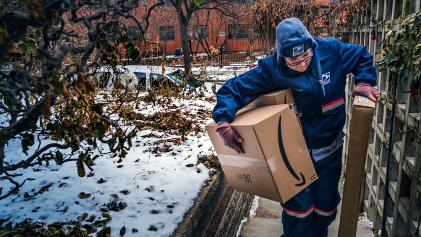 United States Postal Service worker Missie Kittok, who has been a letter carrier for 15 months, help