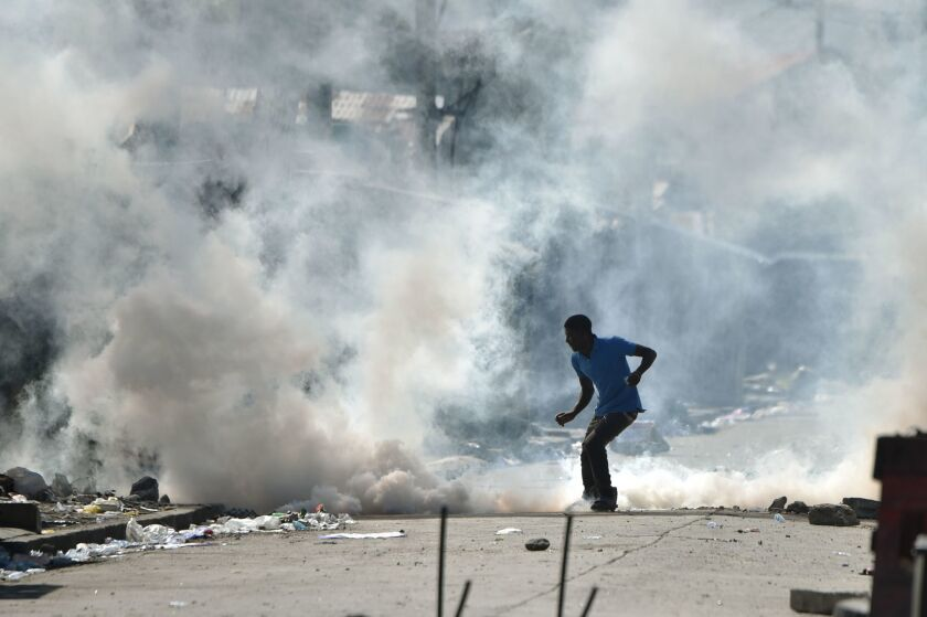 A man kicks a tear-gas canister fired by police during clashes in the Haitian capital, Port-au-Prince, on Nov. 29, 2016.