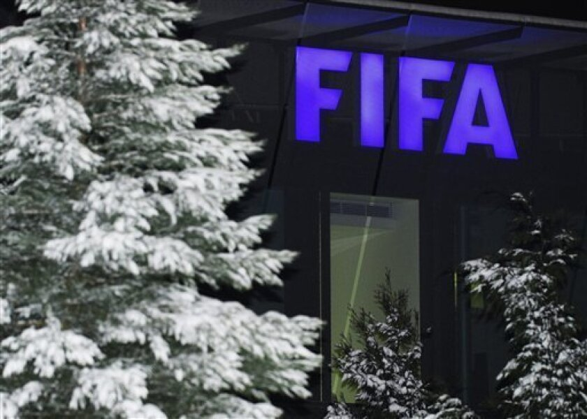 FILE - In this Dec. 2, 2010 file picture a snow covered tree and the FIFA logo are photographed at the FIFA headquarters in Zurich, Switzerland. FIFA has lifted a threat to suspend Switzerland from world football after the national association disciplined FC Sion in a dispute over ineligible players. FIFA says its emergency committee decided that the Swiss FA fulfilled a demand to deal with Sion by a Jan. 13 2012 deadline. Swiss club FC Basel is now cleared to play Bayern Munich in the Champions League round-of-16 next month, and the national team will host Argentina in a Feb. 29 friendly. (AP Photo/Keystone/Steffen Schmidt,File)