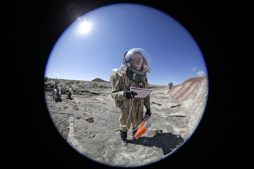 In this photo taken on Saturday, April 18, 2015, Auriane Canesse, crew geologist and health and safety officer, of Crew 153, takes magnetic readings of the ground using a large rectangular apparatus near the Mars Desert Research Station, in Hanksville, Utah. This isn't Mars, but it's resemblance to