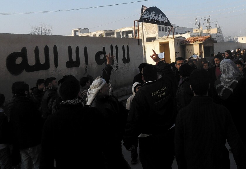 People gather outside the offices of the Islamic State of Iraq and Syria in the city of Aleppo to demand an end to fighting among rebel groups.