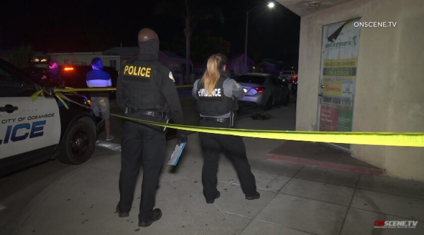 Oceanside police and evidence techs investigate the scene where a man was stabbed Tuesday night outside El Torito Market.