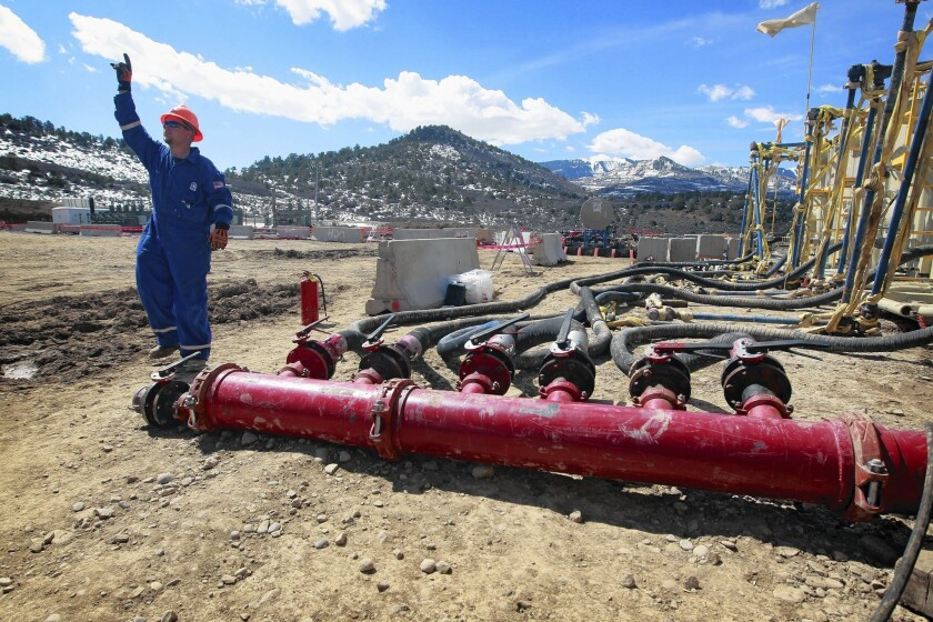 A worker gives a hand signal over the sound of massive pumps at an Encana Oil & Gas fracking site outside Rifle, Colo. Last fall an environmental group estimated that at least 250 billion gallons of water had been used since 2005 in fracking wells in 17 states.